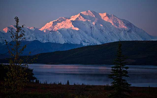 Mount McKinley, tinged pink with alpenglow, with Wonder Lake in the foreground NPS Photo / Jacob W. Frank