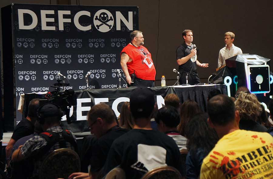 Rogers and Mahaffey (left to right) explain at a Def Con event, what Tesla does right and where the weakness was in designing the Model S' information systems