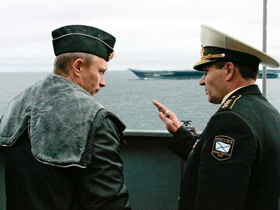 Russian President Putin and Defence Minister Ivanov share a joke while visiting military exercises in the Russia's Arctic North on board nuclear missile cruiser Pyotr Veliky. Photo: REUTERS/ITAR-TASS