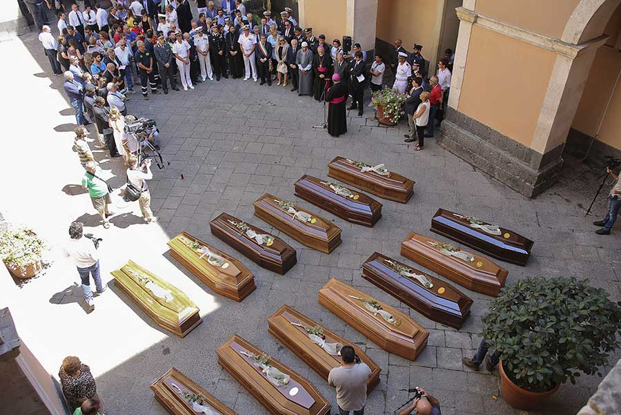 Coffins of 13 migrants who died in the worst shipwreck in the Mediterranean, on 19 April 2015, are seen during an inter-faith funeral service in Catania, Italy. More than 700 people, most of them locked below deck, were believed to have drowned(Antonio Parrinello/Reuters)