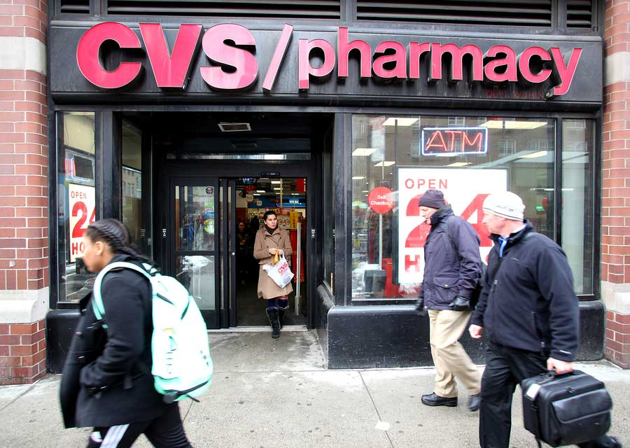 Smokers walk past a CVS Pharmacy n New York City on Tuesday, February 18, 2014. CVS is the retail division of CVS Caremark.