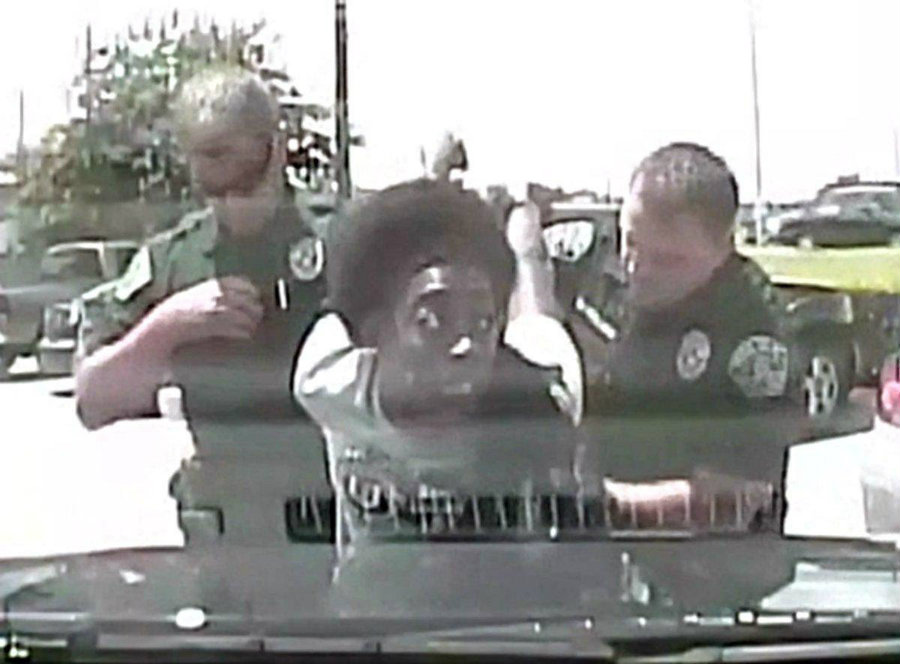 "The woman shouts and resists the officers touch as she asks ""Why are you doing this to me?"" the officer tries getting King on the ground, as she pulls up. Image Credit: YouTube"