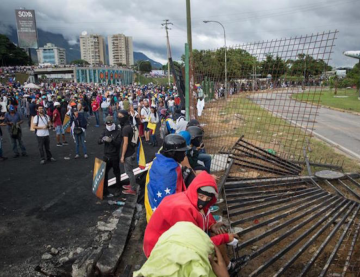 """Protesters tear down security fence at the """"Great General Francisco de Miranda"""" military base. Image Credit: EFE"""
