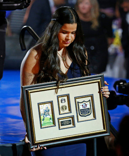 Sydney Seau accepted a framed remembrance of her father, Junior Seau, at the Pro Football Hall of Fame's Gold Jacket Ceremony in Canton, Ohio, on Thursday. Credit: Gene J. Puskar/Associated Press