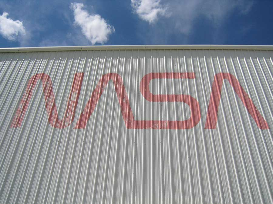 "The NASA Logo (The ""Worm"") on the side of the High-Bay. The Worm was retired in 1992 in favour of the old NASA Insignia (The ""Meatball""). This should give you a good idea of the last time the exterior of the high-bay was painted. Credits: Ketiltrout"