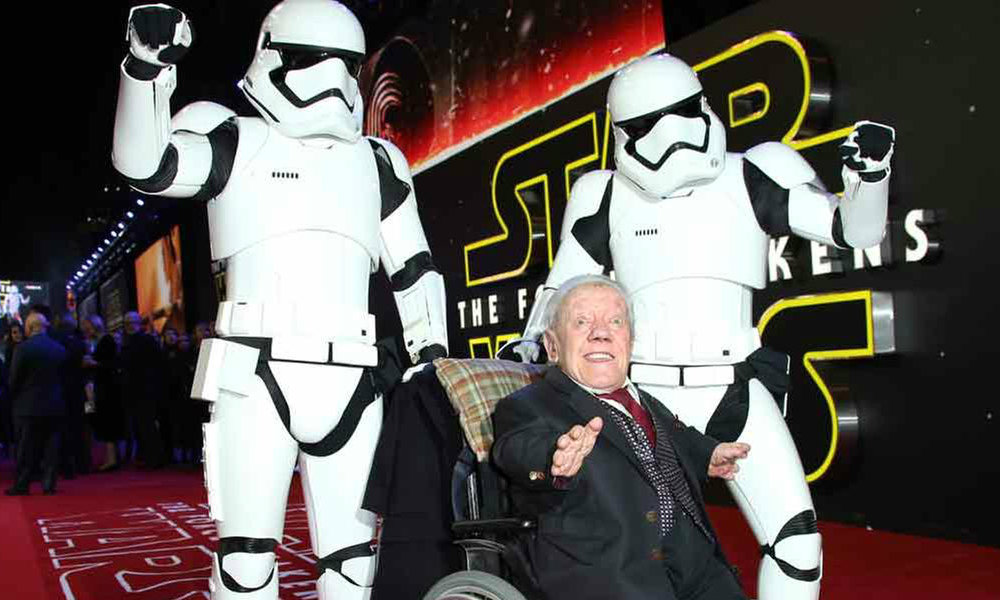 Kenny Baker, center, poses for photographers upon arrival at the European premiere of the latest Star Wars movie, The Force Awakens. Image Credit: EW