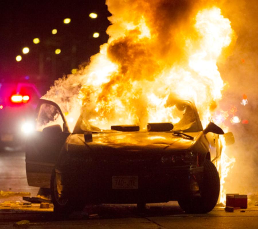 Demonstrators have burned a car. Image credit: Calvin Mattheis Journal-Sentinel via AP.