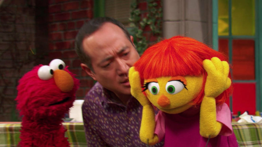 Julia covers her ears as loud siren sounds, and Alan explains to the other Muppets that she doesn't like loud noises. Image credit: Goodstuffbuzz.com